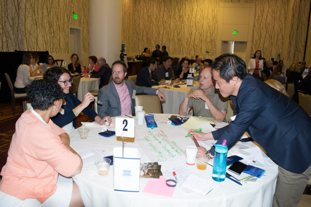 Photo of a group of people talking at a table at an event