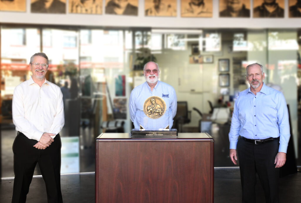 Three smiling men stand apart from each other in front of a glass building and behind an award.